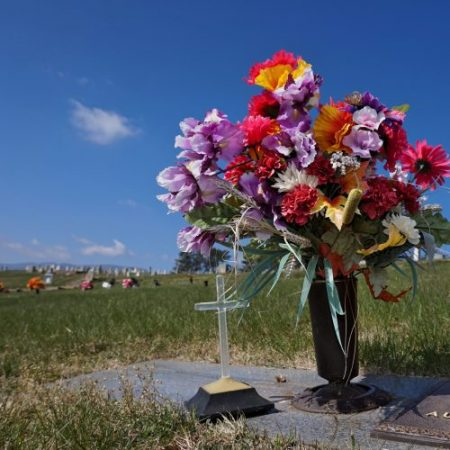 Flowers and cross on headstone with burial plots for sale in Haywood County, NC Bethel Community Cemetery.
